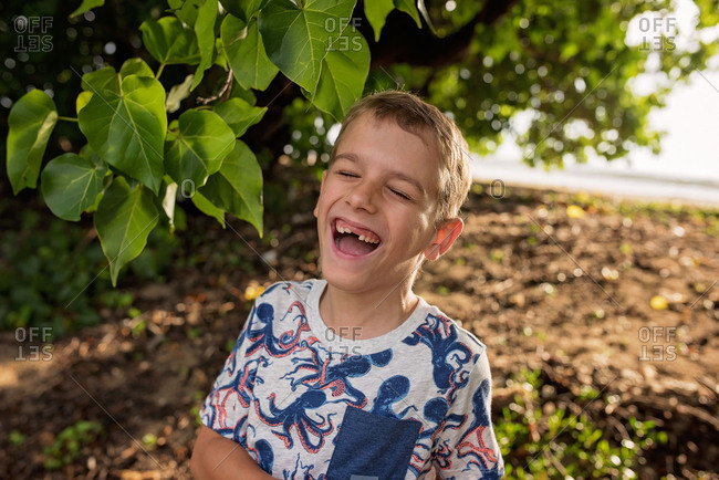 Happy boy standing by a tree on a beach