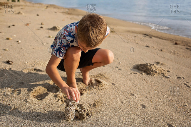 Boy exploring a beach at sunset