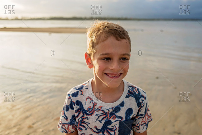 Happy boy on a beach at sunset