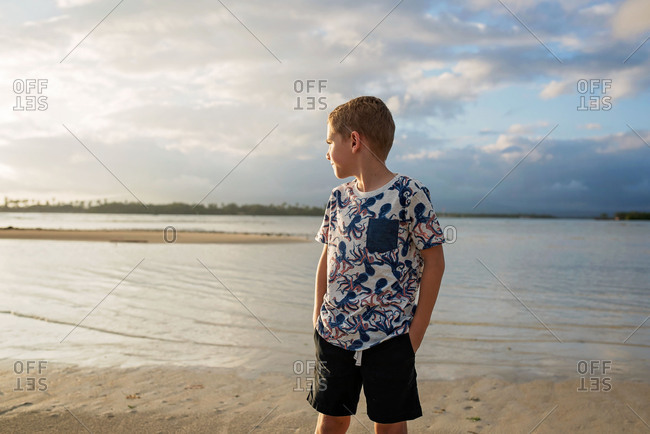 Boy on a beach at sunset looking into the distance