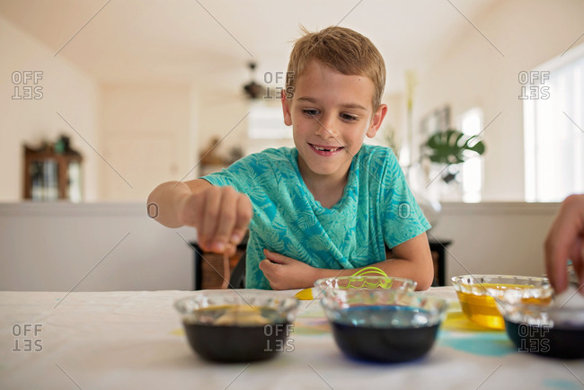 Boy sitting at kitchen counter dying Easter eggs