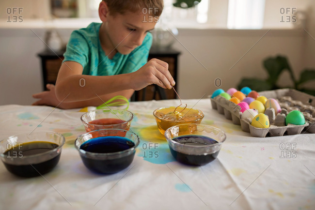 Boy at kitchen counter dying Easter eggs