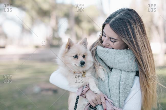 Female owner proudly holding dog close