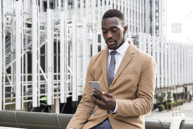 Young black professional checking phone in the city