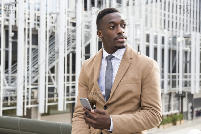 Black Madrid businessman looking up from phone outside