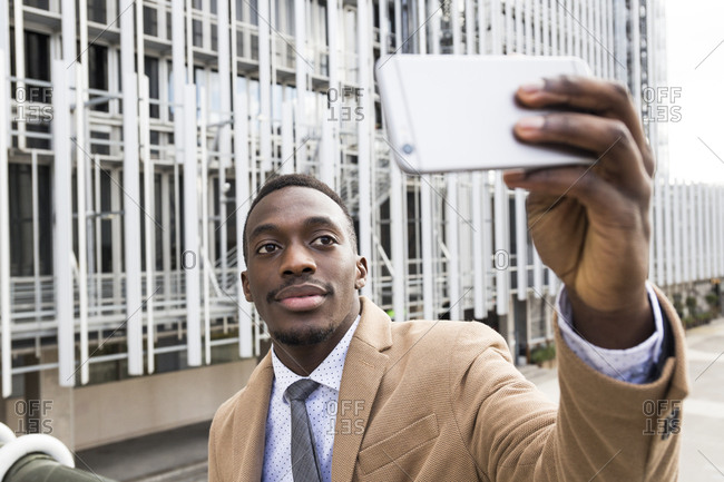 Black man in a suit taking a selfie photo with his smartphone