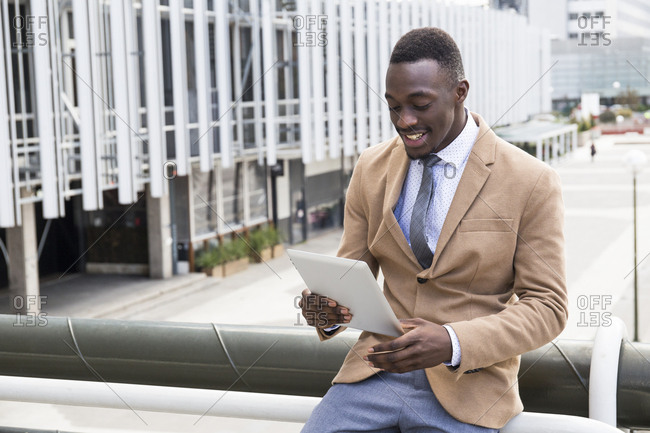 Young professional man watching something funny on his tablet outside