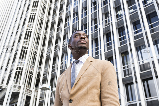 Low angle vie of young black professional man staring off camera in front of building