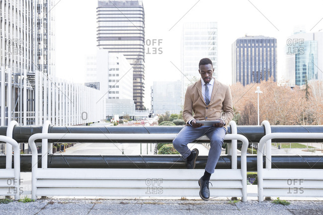 Young black Madrid businessman sitting on railing with tablet
