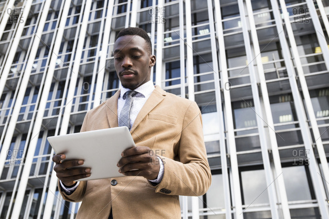 Young black Madrid businessman on tablet in front of modern office complex