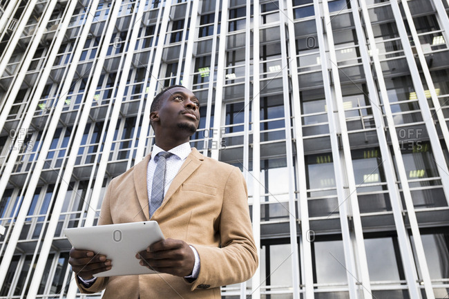 Contemplative black man looking up from tablet