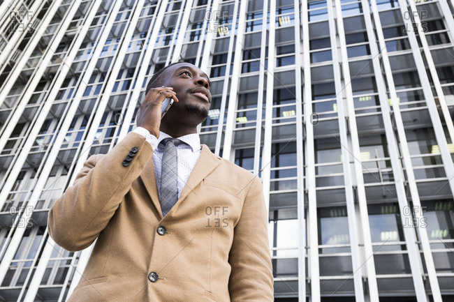 Lower angle view of black man talking on smartphone in front of office building