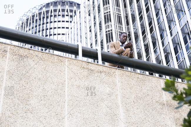 Black man leaning over wall railing using his phone