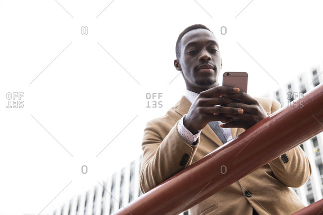 Low angle view of black man standing at railing in front of modern building to check his phone