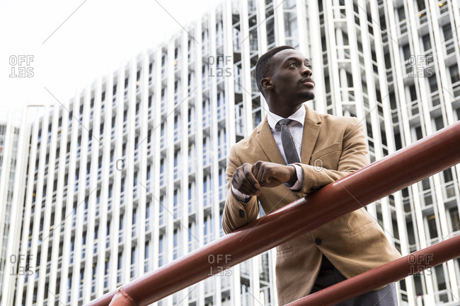 Man leaning on a railing in sharp suit jacket in business district