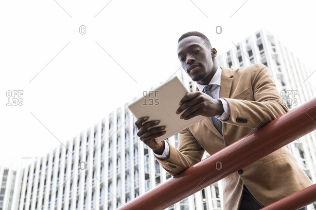 Black man leaning over railing looking at his tablet in Madrid, Spain