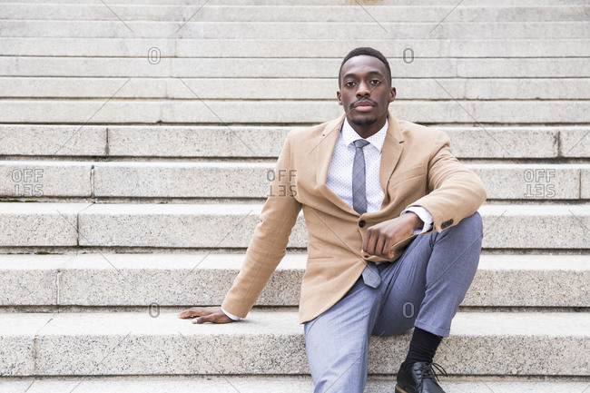 Young black Madrid businessman sitting on outdoor concrete stairs