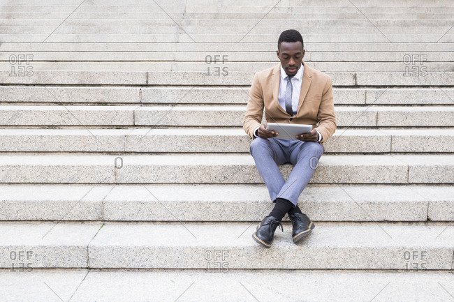 Black man using tablet on city building stairs