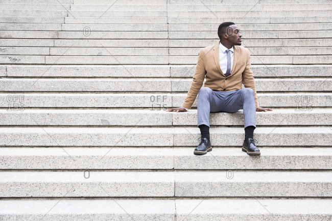 Madrid man sitting on stone steps looking off to the side