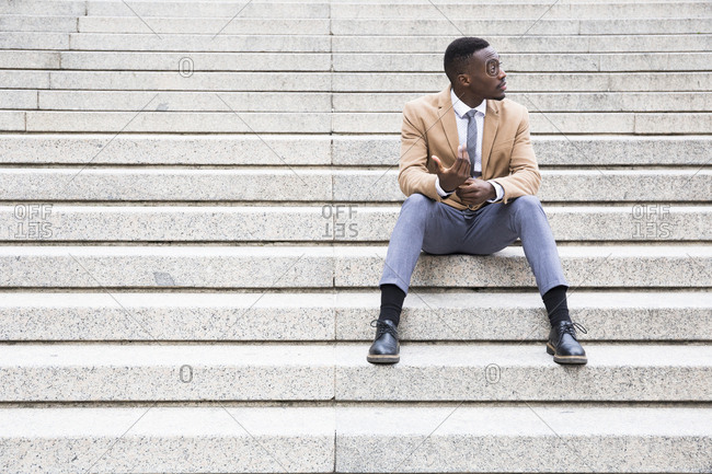 Young black Madrid businessman sitting on stone steps