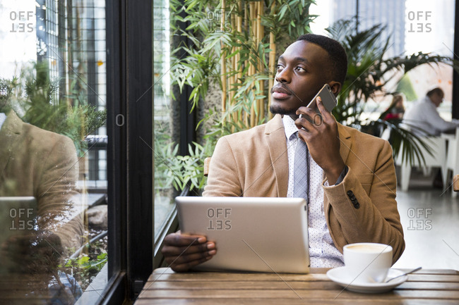 Multitasking man with tablet looking out cafe window during phone conversation