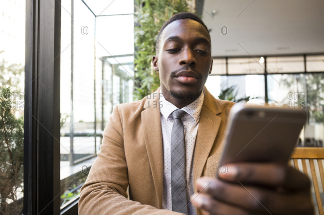 Black man checking smartphone in a cafe in Madrid, Spain