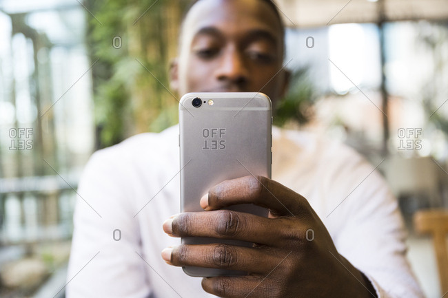 Young black Madrid businessman taking photos with smartphone