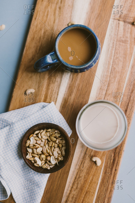 Top view of coffee, milk, and cashews on wooden board