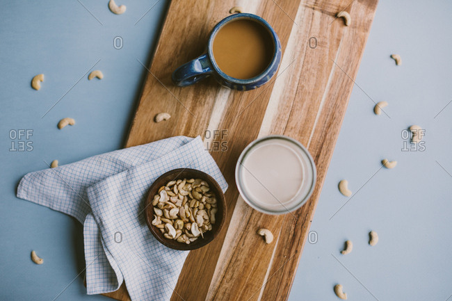 Cashew milk and coffee with ingredients on countertop