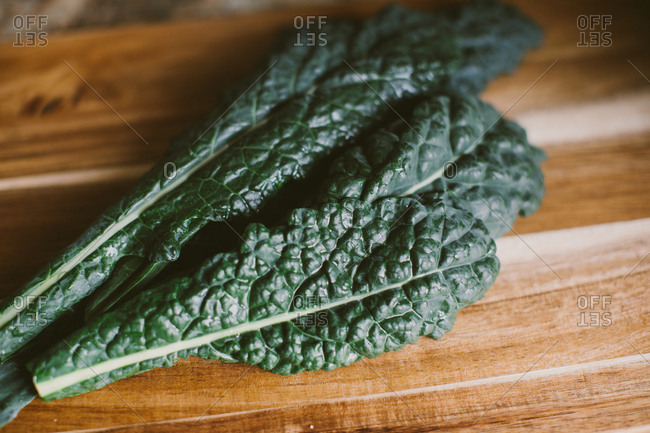 Fresh clean kale leaves on kitchen cutting board