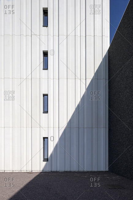 Clean diagonal shadow cast on functional exterior wall of office building