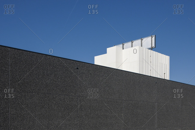 Black granite wall cutting diagonally across blue sky
