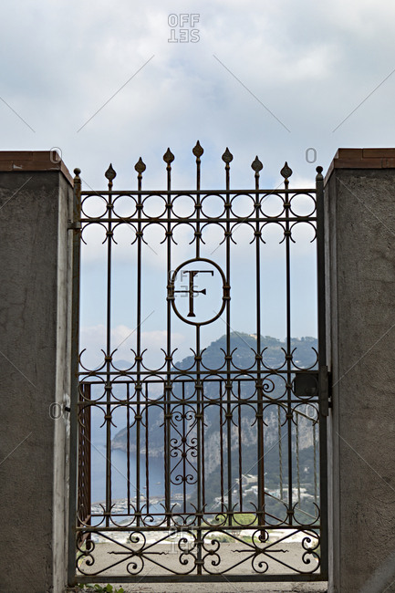Iron gate in wall opening at overlook of the coastline of the Italian island of Capri