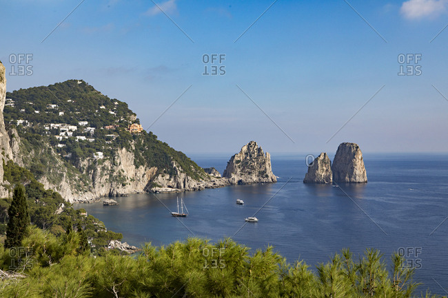 Scenic view of coastal village and ships in a bay along the rocky coast of the Italian island of Capri