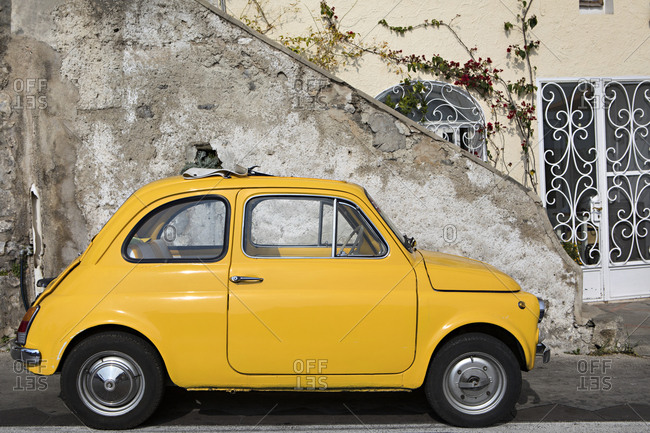 Positano, Italy - October 19, 2017: Small yellow car parked in front of historic building in an Italian village