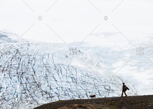 Man walks with his dog along the Harding Ice Field in Seward Alaska.