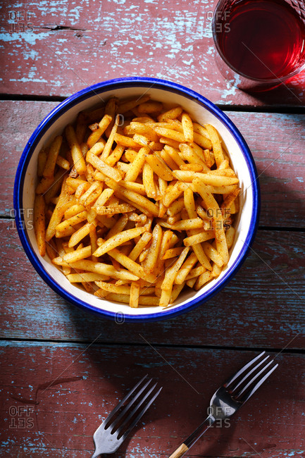 French fries served in a plate on rustic wooden background