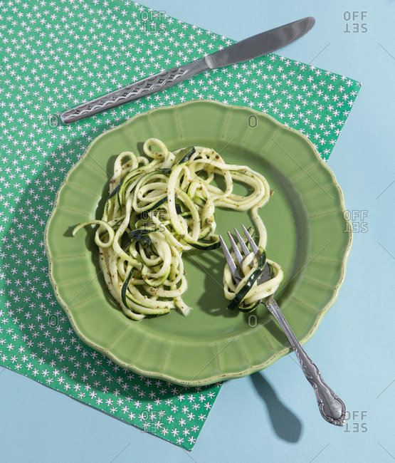 Plate of zucchini noodles with pesto and knife and fork