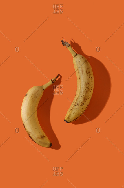 Spotted bananas on orange backdrop