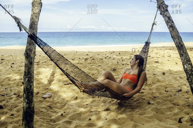 Woman lying in hammock looking at the sea in Costa Rica.