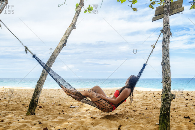 Woman lying in hammock looking at the sea in Costa Rica