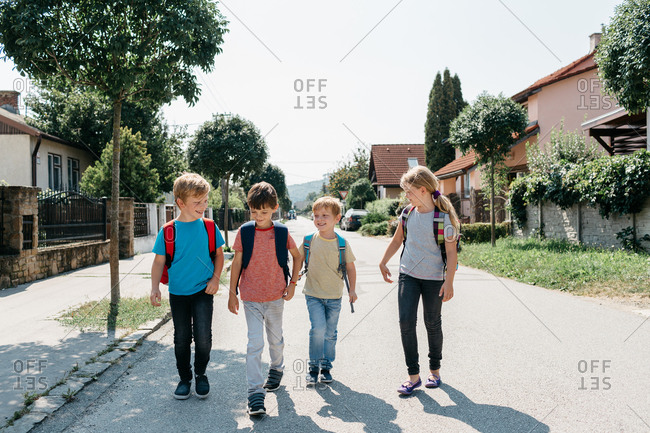 School children walking to school unaccompanied by an adult. Classmates going home from school on their own talking to each other.