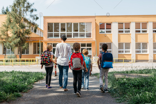 Children on the way to school with an adult supervision. Rear view of a group of children walking to school accompanied by a parent volunteer.