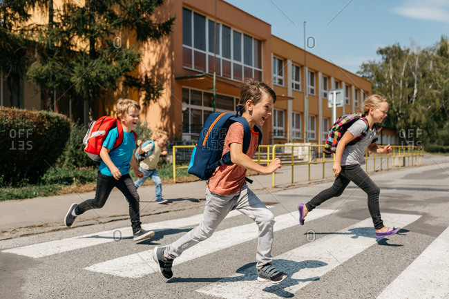 A group of laughing classmates rushing out of school crossing road. Happy children running across a road at a pedestrian crossing.