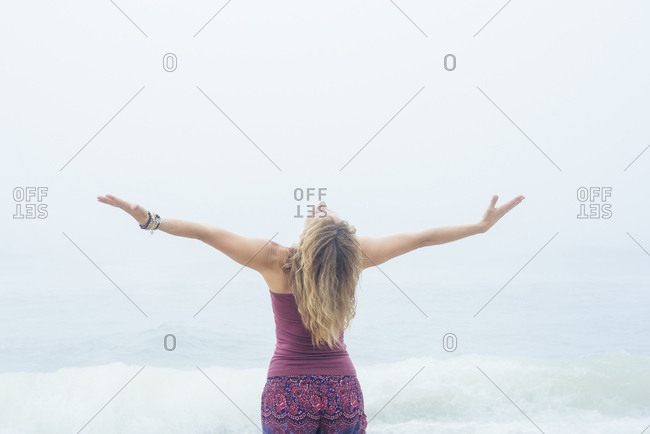 Rear view of mature woman with arms outstretched standing at beach against sky