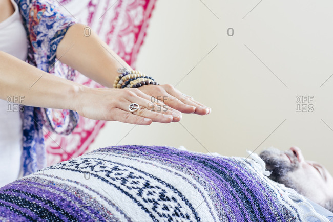 Cropped image of woman performing reiki on mature man at spa