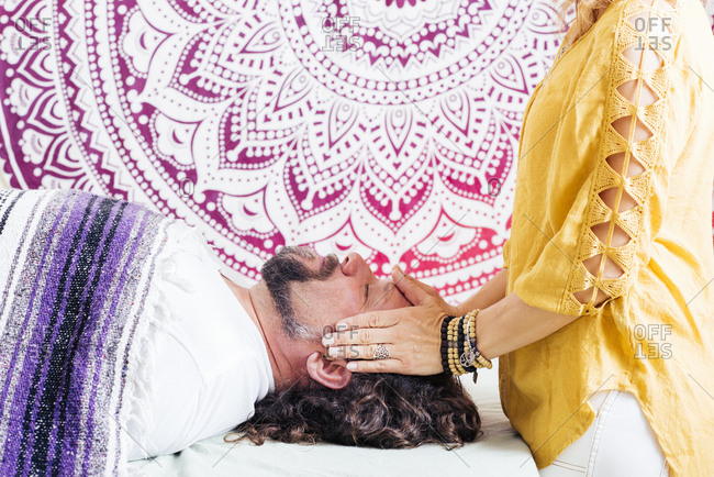 Midsection of woman performing reiki on mature man's head in spa