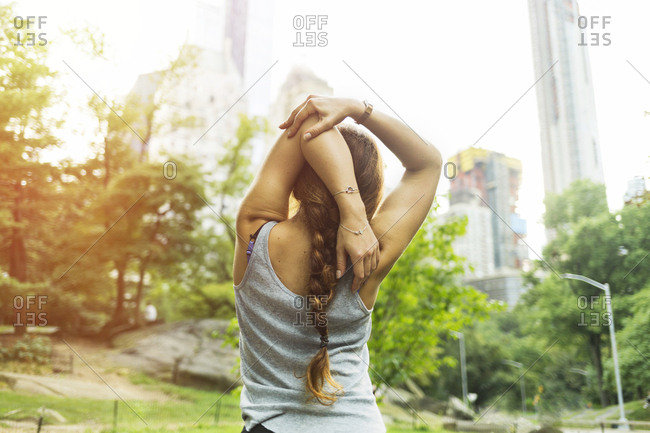 Rear view of fit young woman stretching  in park