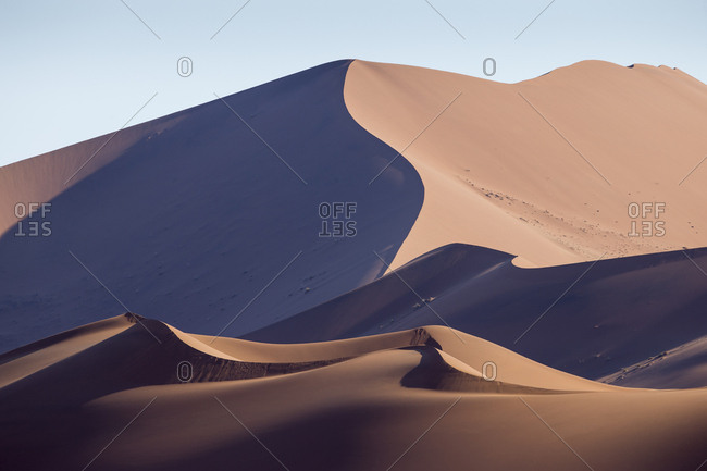 Africa, Namibia, Namib Naukluft National Park, Morning sun lights windblown red sand dunes in Namib Desert near Sossusvlei