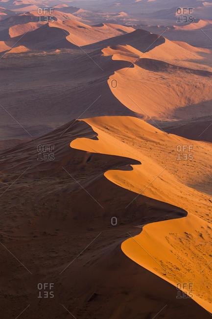 Africa, Namibia, Namib Naukluft National Park, Aerial view of morning sun lighting windblown red sand dunes in Namib Desert near Sossusvlei
